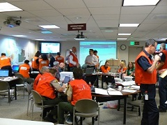 Picture of 20 emergency workers in an office building wearing orange vests talking in small groups