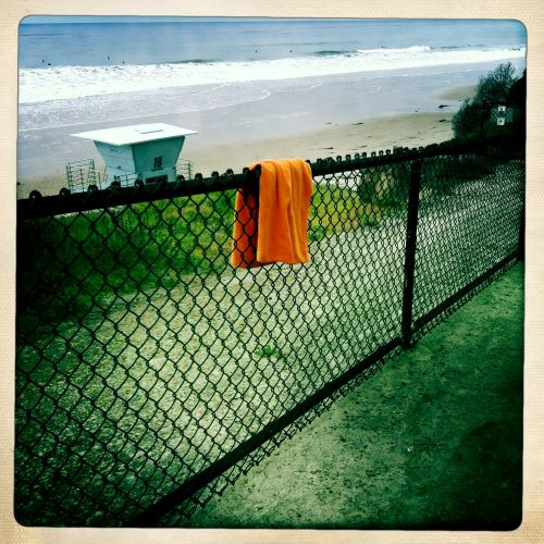 Cardiff Campgrounds view to the west from a chain link fence with an orange towel hanging over it; a view of a lifeguard tower, the beach, and the ocean down below